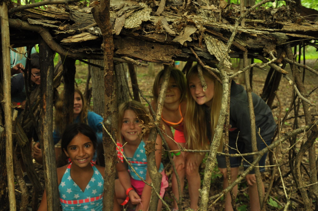 Kids learning how to build an outdoor shelter at camp